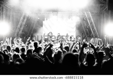 Silhouettes of people at a concert in front of the scene in bright light. Black and White