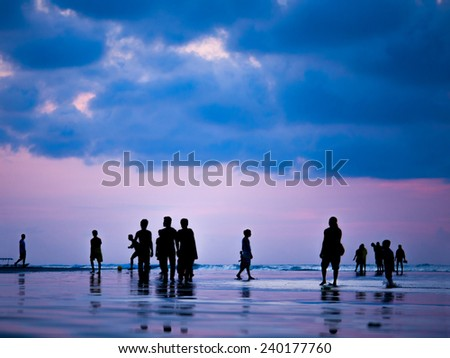 Silhouettes of people at sunset on the beach of Kuta Bali Indonesia - stock photo
