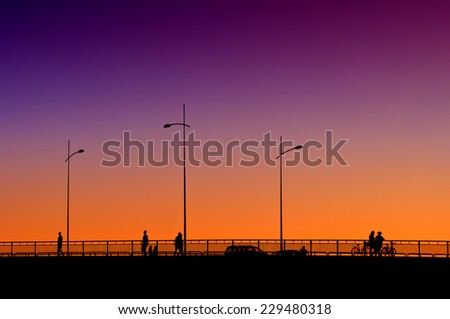 Silhouettes of people crossing the bridge in sunset by car and by foot. - stock photo