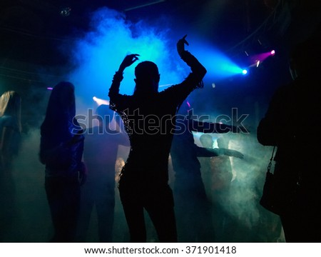 silhouettes of people dancing in the fog highlighted with night club lighting equipment