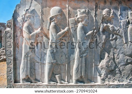 Silhouettes of people in ancient costumes on the destroyed stone bas-relief in famous city Persepolis, modern Iran. Persepolis was a capital of the Achaemenid Empire (550 - 330 BC).  - stock photo