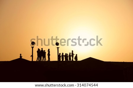 Silhouettes of people in the desert at sunset, hiking, walking, summer heat - stock photo