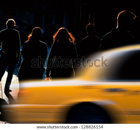 Silhouettes of people on back lit street, trying to catch a cab - stock photo
