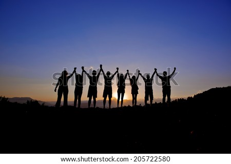 silhouettes of people on mountains - stock photo