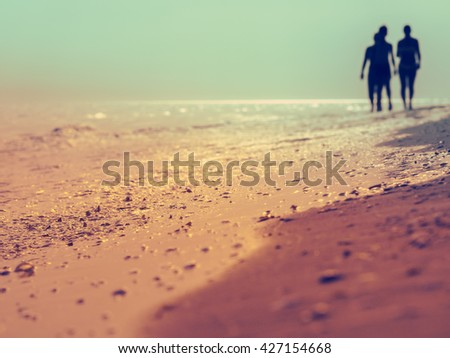 Silhouettes of people on sandy beach at sunset, soft light and instagram effect. Young people on sand beach in the evening, romantic landscape at summer holidays. - stock photo