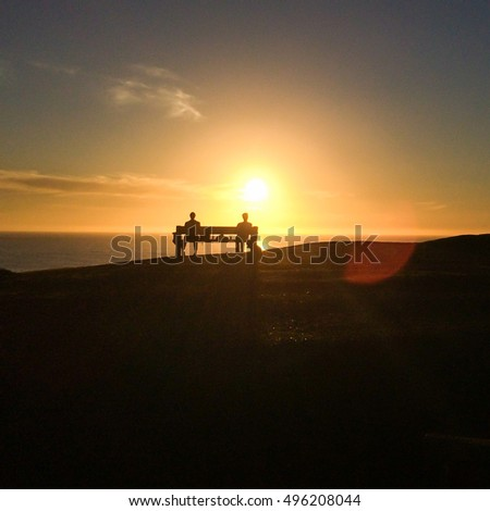 Silhouettes of people on the bench enjoying sunset