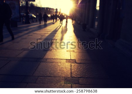 silhouettes of people on the cobblestone pavement at sunset - stock photo