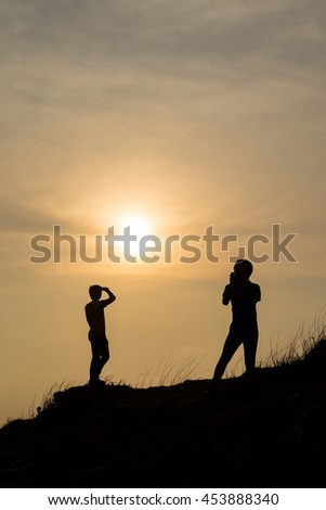 Silhouettes of people standing on the mountain. In the evening, the sun was falling. - stock photo