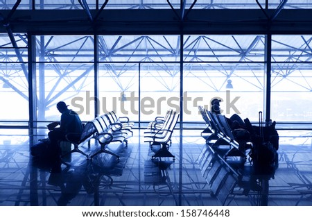 Silhouettes of people traveling on airport; waiting at the plane boarding gates. - stock photo