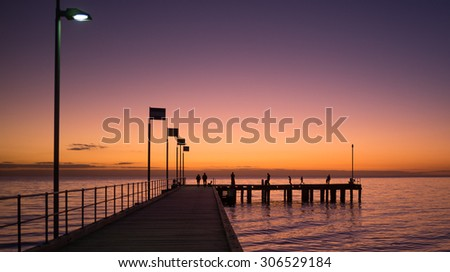 Silhouettes of people walking on a pier at sunset, Victoria, Australia - stock photo