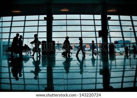Silhouettes of people with luggage walking at airport Sheremetyevo, Moscow, Russia - stock photo