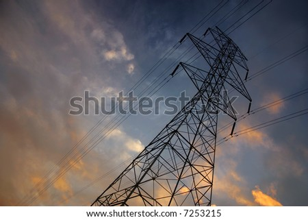 Silhouettes of power lines and a tower with a brilliant sunset - stock photo