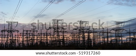 silhouettes of power lines on sunset background