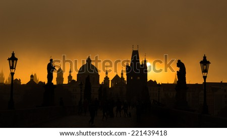 Silhouettes of Prague towers and statues on Charles bridge during sunrise - stock photo