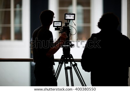 Silhouettes of professional operator taking video  - stock photo