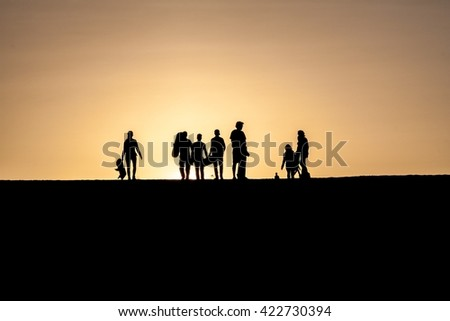 Silhouettes of sand boarders during the sunset near desert oasis Huacachina near Ica, Peru - stock photo