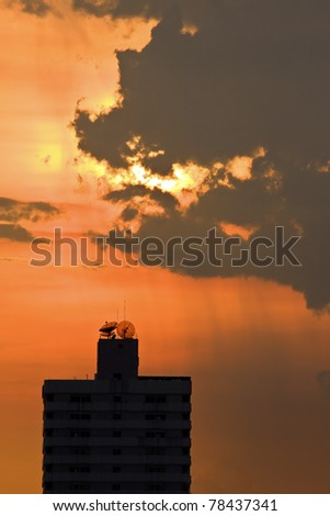 silhouettes of Satellite dishes on the top of building - stock photo