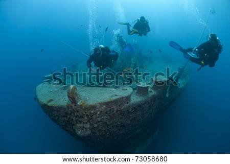 Silhouettes of scuba divers exploring the bow of the SS Thistlegorm shipwreck. SS Thistlegorm, Straights of Gubal, Red Sea, Egypt.