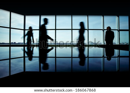 Silhouettes of several office workers on background of window - stock photo