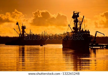Silhouettes of ships arriving in the harbor at sunset - stock photo