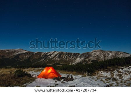 Silhouettes of snowy mountain peaks and edges night sky with many stars and milky way on background illuminated orange tent on foreground - stock photo