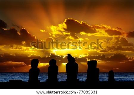 Silhouettes of standing moai against dramatic orange sunset - stock photo