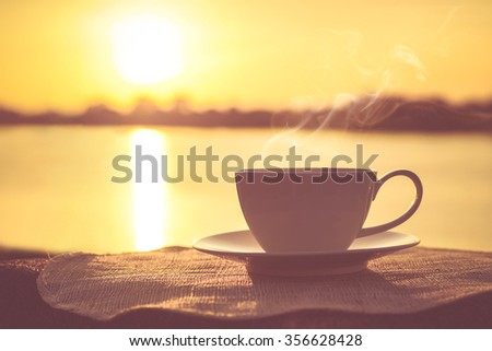 Silhouettes of sunrise morning coffee with a note and a pen - stock photo