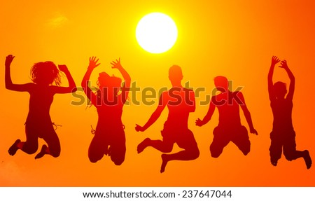 Silhouettes of teenage boys and girls jumping high in the air on sunny summer day. - stock photo
