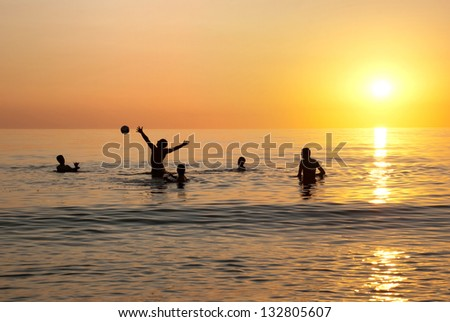 Silhouettes of teenagers playing ball at the water.