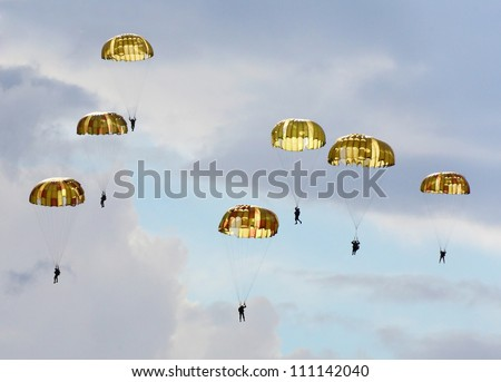 Silhouettes of the army skydiver team against dramatic sky. - stock photo
