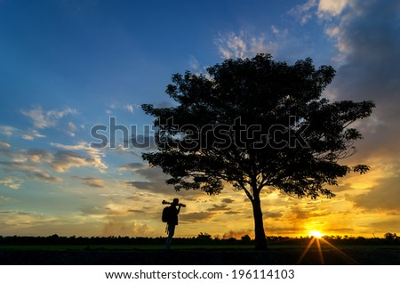 Silhouettes of the trees and photographer. Beautiful sunset sky