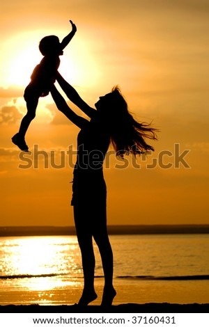 Silhouettes of the women and child on sundown