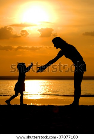 Silhouettes of the women and little girl on sundown