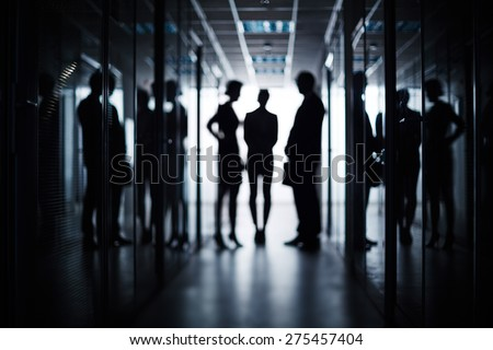 Silhouettes of three business people standing in corridor of office building - stock photo