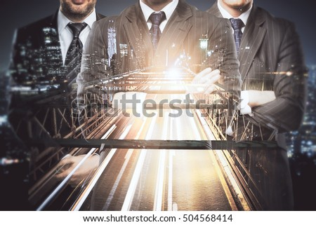 Silhouettes of three businesspeople in suits and with folded arms on abstract night city road background. Double exposure. Teamwork, partnership and leadership concept
