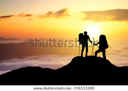 Silhouettes of tourist team on mountain peak. Sport and active life concept - stock photo