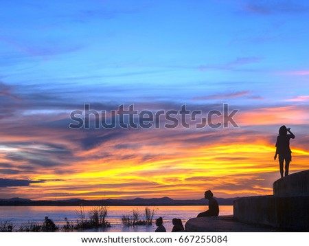 Silhouettes of tourists under a brightly-coloured sunset sky seen from the steps of the Mekong River, Vientiane, Laos