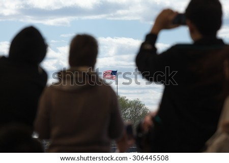 Silhouettes of travelers looking at the flag of the United States of America. - stock photo