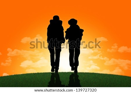 silhouettes of two backpackers, a man and a woman, walking together on a top of the hill towards the sunset - stock photo