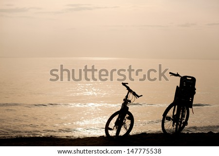 Silhouettes of two bikes on the coast during sunset - stock photo
