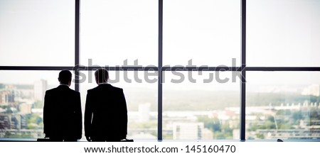 Silhouettes of two businessmen standing by the window - stock photo