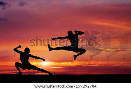 Silhouettes of two fighters on sunset fiery background. - stock photo