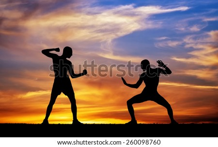 Silhouettes of two fighters on sunset fiery background  - stock photo