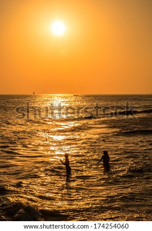 silhouettes of two girls at sunset, swimming in the sea