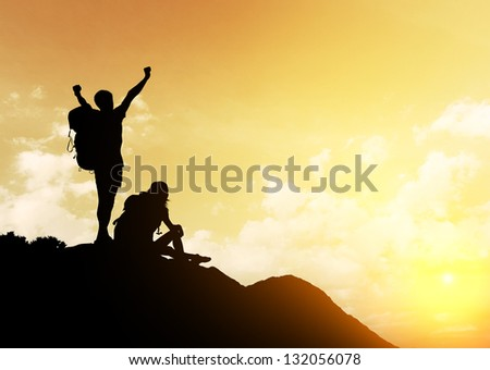 Silhouettes of two hikers with backpacks enjoying sunset view from top of a mountain - stock photo