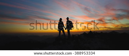 Silhouettes of two hikers with backpacks enjoying sunset view from top of a mountain. Travel concept - stock photo