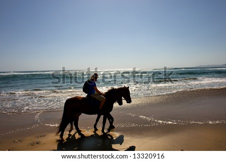 Silhouettes of two horse riders on beach. Shot in Sodwana Bay Nature Reserve, KwaZulu-Natal province, Southern Mozambique area, South Africa.