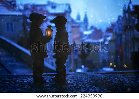 Silhouettes of two kids, standing on a stairs, holding a lantern, view of Prague behind them, snowy evening - stock photo