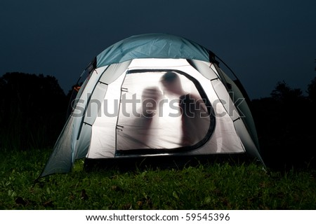 Silhouettes of two lovers in tent - stock photo