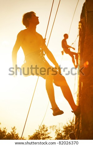 Silhouettes of two men climbing on a cliff at sunset